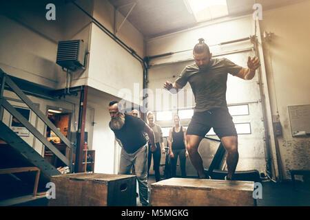 Zwei passen Männer Box springt während ein Fitnessstudio Training Session mit Freunden beobachten im Hintergrund - Stockfoto