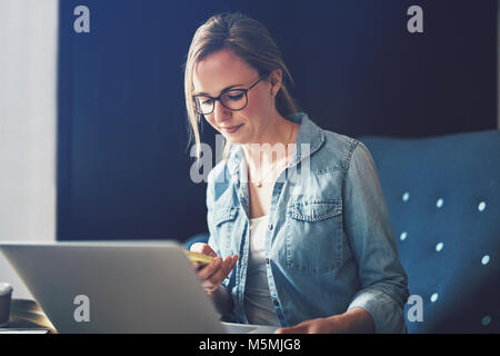 Lächelnden jungen Geschäftsfrau, sitzen auf einem Sofa, die an einem Notebook arbeitet und SMS-Nachrichten auf Ihrem - Stockfoto