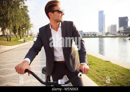 Geschäftsmann Reiten Fahrrad an städtischen Straße morgen arbeiten - Stockfoto