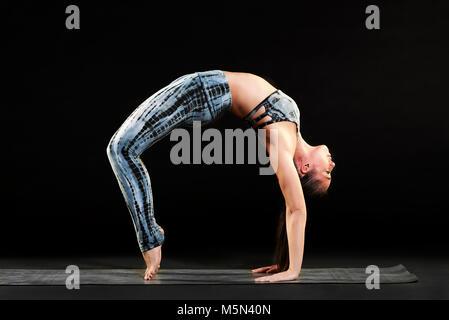 Geschmeidig Frau demonstriert das Rad stellen im Yoga Balancing Während wölbt den Rücken mit Füßen und Händen auf - Stockfoto