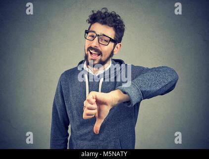 Junge Bartgeier Hipster in Gläsern Daumen nach unten zeigen und Lachen in Mock. - Stockfoto