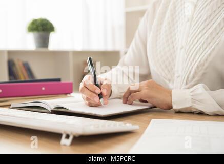 Berufstätige Frau schreiben Sie Termine oder Hinweise Terminplan für die Planung der Arbeiten in Ihrem Büro - Stockfoto