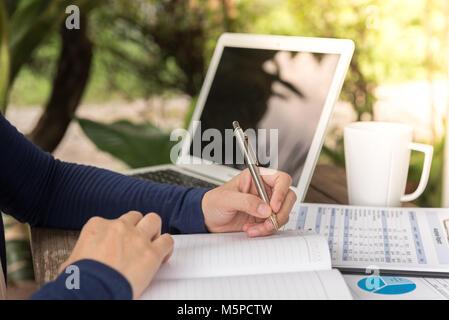 Frau schreiben Tagebuch oder Agenda und die Arbeit mit Notebooks Computer zu Hause. student Education Notes im Notebook - Stockfoto