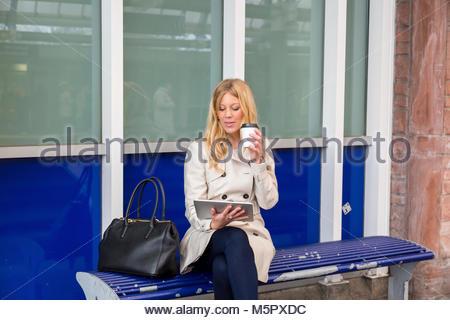 Junge Frau auf einer Bank sitzen, Warten, Warten, Zug - Stockfoto