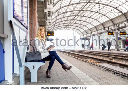 Attraktive junge Frau warten auf einen Zug - Stockfoto