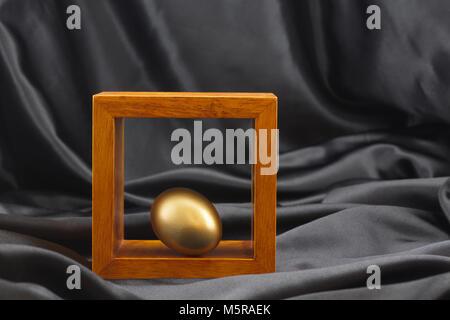 Gold Ei durch Platzierung in Holz Rahmen gegen Schwarz Satin Hintergrund akzentuierte unterstreicht die Bedeutung - Stockfoto