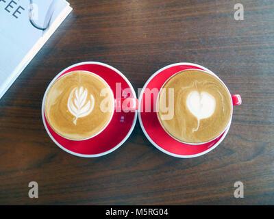 Zwei latte Art Kaffeetassen auf hölzernen Tisch Stockfoto