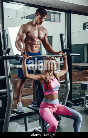 Sport, Fitness, Teamarbeit, Bodybuilding und Personen Konzept - junge Frau und persönlicher Trainer mit Barbell - Stockfoto
