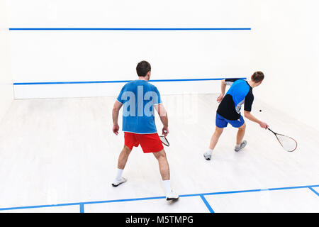 Rückansicht des Squash Spieler Schlagen einer Kugel in einem Squashplatz. Squash Spieler in Aktion. Männer spielen - Stockfoto