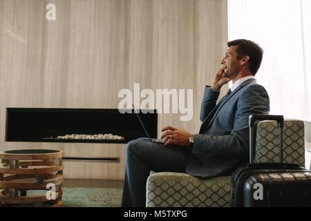 Seitenansicht der lächelnden Geschäftsmann mit Laptop Gespräch am Handy warten am Flughafen Lounge. Geschäftsreisende - Stockfoto