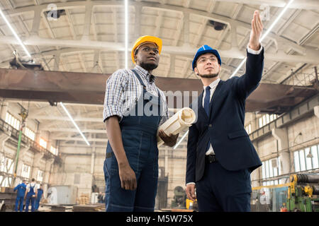Zuversichtlich Inspektor im klassischen Anzug, der auf etwas, während junge Techniker mit Blaupause in Händen, die - Stockfoto