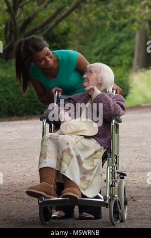 Multikulturelle junge Frau Pflegeperson Unterstützung Arbeiter drücken geriatrische Dame im Rollstuhl im Park - Stockfoto