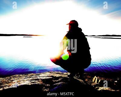 Einsamer Mann, Wanderer sitzt alleine an der felsigen Küste und genießen den Sonnenuntergang. Blick über die felsige - Stockfoto