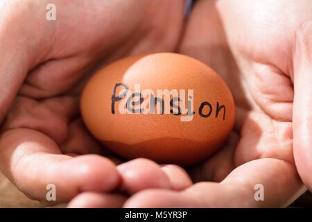 Nahaufnahme einer menschlichen Hand mit braunen Ei anzeigen Pension Text - Stockfoto