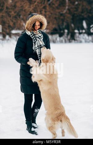 Bild der Frau in den schwarzen Jacke mit Retriever auf Spaziergang im Winter Park