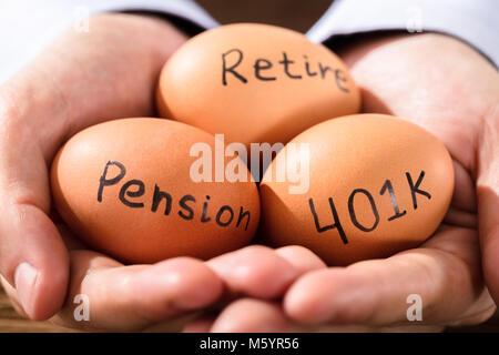 Nahaufnahme einer menschlichen Hand mit braunen Ei Übersicht Rente und Ruhestand Text - Stockfoto