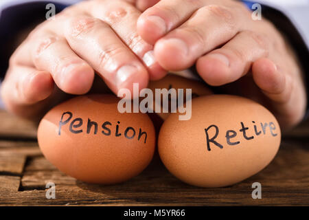 Nahaufnahme von einer Person schützende Hand Braun Ei Übersicht Rente und Ruhestand Text - Stockfoto