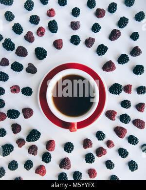 Ovaler Rahmen aus köstlichen frischen Sommer Brombeeren und Himbeeren mit einem roten Tasse Tee in der Mitte. Minimalismus - Stockfoto
