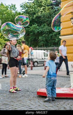 Kinder spielen mit großen Blasen an Olha Kobylianska Street Fußgängerzone in Czernowitz, Region Bukowina, in der - Stockfoto