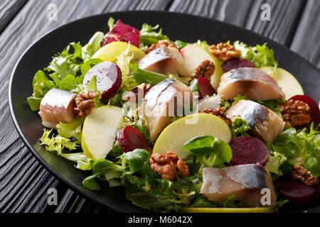 Frisch Makrele Salat mit Äpfeln, Nüssen, Rüben und mix Salat close-up vorbereitet auf schwarzem Teller auf dem Tisch. - Stockfoto
