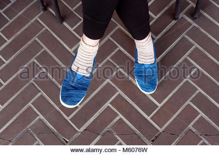 Sitzende person Tragen komfortabel blauen Stoff Schuhe - Stockfoto