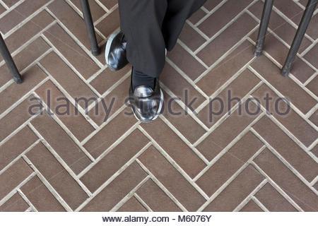 Sitzende Person tragen glänzende schwarze Schuhe - Stockfoto