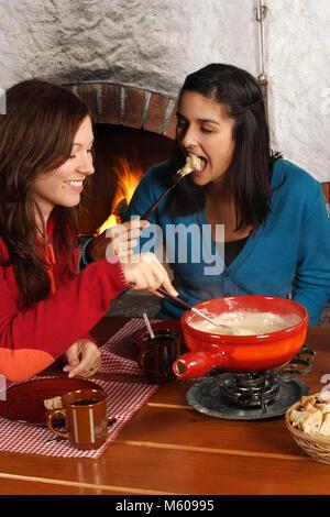 Foto von zwei schönen Frauen Brot eintauchen in das geschmolzene Käse in ein Fondue Topf. Fokus auf Mädchen auf - Stockfoto