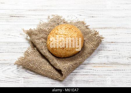 Frisch gebackenes Brot oder Brötchen Mit Sesam und Sonnenblumenkerne auf hölzernen Tisch. - Stockfoto