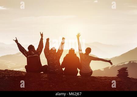 Gruppe von vier glückliche Freunde ist Spaß mit erhobenen Händen gegen Sonnenuntergang in den Bergen - Stockfoto