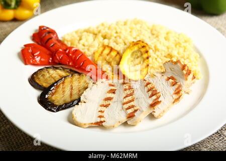 Gegrilltes Hähnchen mit Scheiben, mit Gemüse, Bulgur auf einem weißen Teller. Im Hintergrund, Salatblätter, Farbe - Stockfoto