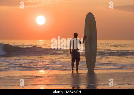Surfer mit Longboard stehen am Strand bei Sonnenuntergang Wellen - Stockfoto