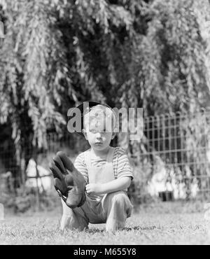 1940 Kleine ernsthafte blonde Junge HOLDING EINEN BASEBALL HANDSCHUH TRAGEN BASEBALL CAP IM GRAS-b 18929 HAR 001 - Stockfoto