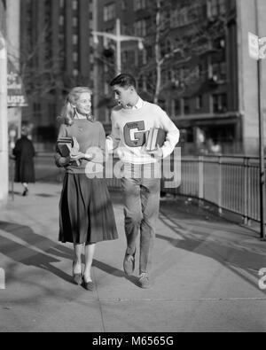 1950er Jahre TEENAGER TRAGEN VARSITYBUCHSTABEN PULLOVER MÄDCHEN ZU FUSS NACH HAUSE NACH SCHULE - bx 018367 CAM001 - Stockfoto