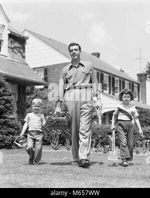 1950 s Vater mit zwei Kindern Tochter und Sohn im VORGARTEN, GARTENGERÄTE, KAMERA-j 1157 HAR 001 HARS SCHWESTER - Stockfoto