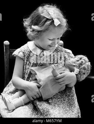 1930er Jahre 1940er Jahre lächelnde blonde Mädchen HOLDING BABY DOLL - j1513 HAR 001 HARS GESUNDHEIT NUR EINE PERSON - Stockfoto