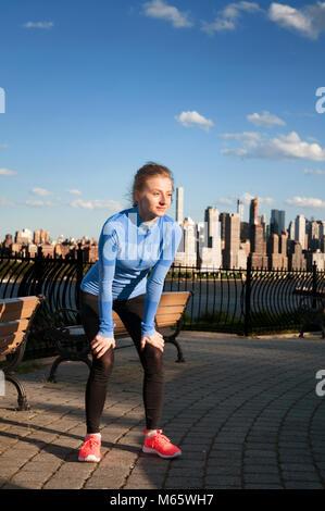 Sport und Fitness. Müde Frau Runner eine Pause nach dem Hart im Park mit Blick auf Downtown Manhattan New York City. - Stockfoto