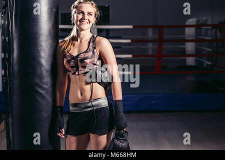 Frau Boxer nach vorne auf einem riesigen Boxsack zu ruhen - Stockfoto