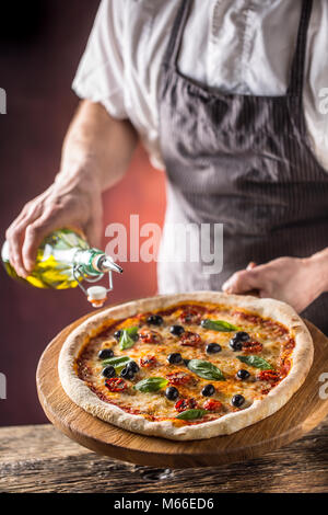 Koch und Pizza. Phef gießen Olivenöl auf Pizza im Hotel oder im Restaurant. - Stockfoto