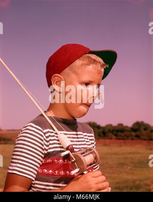 1950er Jahre überrascht JUNGE MIT ZIKADE INSEKT AUF SEINER NASE HOLDING ANGEL DAS TRAGEN DER ROTEN BALL CAP-Kj 13654 - Stockfoto