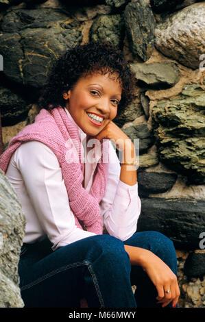 Porträt der jungen afrikanischen amerikanischen Frau in die Kamera lächeln tragen rosa Pullover über die Schultern - Stockfoto