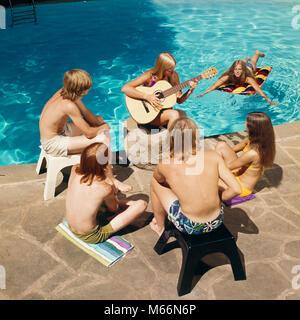 1970 s 6 TEENS RUND UM SCHWIMMBAD hören Mädchen spielte Gitarre-ks 11611 HAR 001 HARS FREUNDSCHAFT halber Länge - Stockfoto