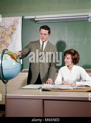1960 s 2 SCHÜLER IM KLASSENZIMMER JUGENDLICH JUNGE STAND VON GLOBE Mädchen sitzt am Schreibtisch KARTE TAFEL HIGH - Stockfoto
