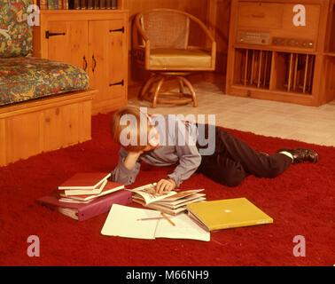 1960er Jahre junge LESEN STUDIUM HAUSAUFGABEN LIEGEN AUF RED shag Teppich IM WOHNZIMMER - KS5520 HAR 001 HARS SCHULEN - Stockfoto