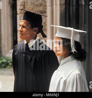 1970 s afrikanische amerikanische Paar TRAGEN GRADUIERUNG ROBEN PORTRAIT-ks 7202 HAR 001 HARS FEIER FRAUEN BRÜDER - Stockfoto