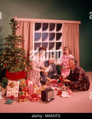 1960er Jahre Mann Frau Mutter Vater zwei Teenager JUNGE MÄDCHEN SOHN TOCHTER UM WEIHNACHTSBAUM Geschenke auszupacken - Stockfoto