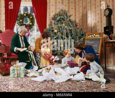 1970 s Familie ÖFFNEN GESCHENKE WEIHNACHTEN MORGEN UM DEN BAUM-kx 7930 HAR 001 HARS KRANZ FREUDE LIFESTYLE FEIER - Stockfoto