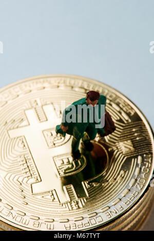 Nahaufnahme von einem Mann, der einen Koffer auf einem Haufen bitcoins gegen einen weißen Hintergrund mit einigen - Stockfoto