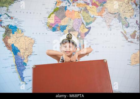 Schöner kleiner Junge in der Captain's Hut wirft die Koffer vor dem Hintergrund der Welt Karte - Stockfoto