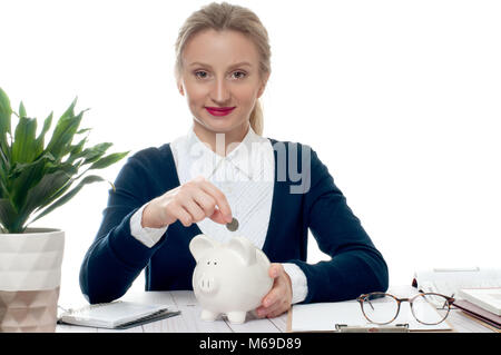 Frau die Münze im Sparschwein. Finanzielle Budget gespart Konzept - Stockfoto
