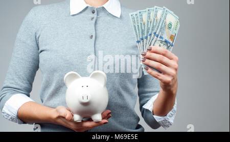 Frau mit Sparschwein und Bündel geld Banknoten. Finanzielle Einsparungen, intelligente Investition Konzept - Stockfoto